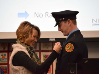 Firefighter/Paramedic Krivanec's mother Denise pins his badge on him.
